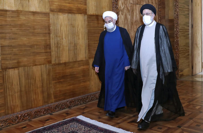 In this photo released by the official website of the office of the Iranian Presidency, President Hassan Rouhani, left, and President-elect Ebrahim Raisi, who is the current judiciary chief, walk during their meeting in Tehran, Iran, Wednesday, June 23, 2021. (Iranian Presidency Office via AP)