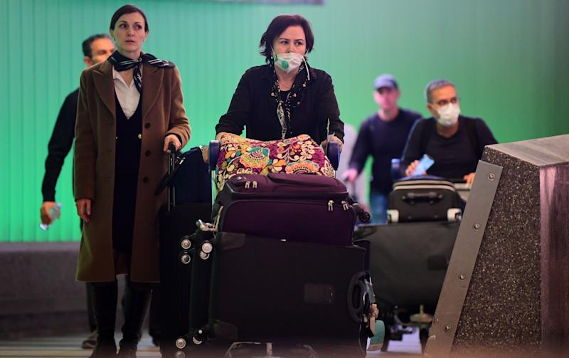 International travelers, some wearing face masks, arrive at Los Angeles International Airport on March 12, 2020, one day before a U.S. flight travel ban hit 26 European countries over the coronavirus. (Photo: FREDERIC J. BROWN via Getty Images)