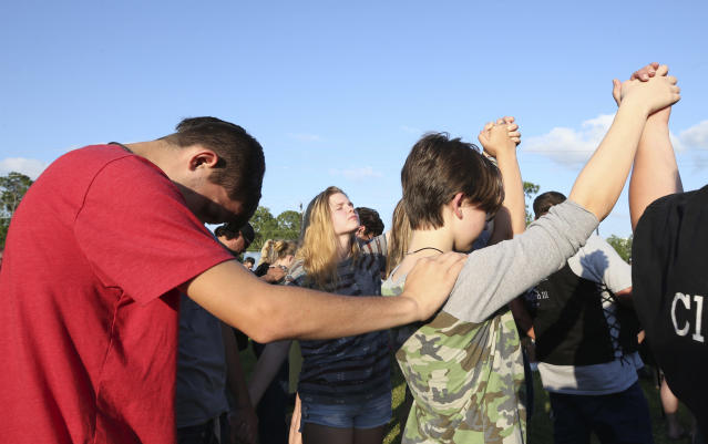 <p>Santa Fe High School students gather in prayer during a vigil following a shooting at Santa Fe High School in Santa Fe, Texas, on Friday, May 18, 2018. Seventeen-year-old Dimitrios Pagourtzis is charged with capital murder in the deadly shooting rampage. (Photo: Jennifer Reynolds/The Galveston County Daily News via AP) </p>