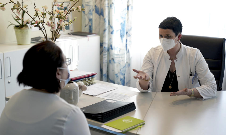 Joerdis Frommhold, right, head doctor of the 'MEDIAN Clinic Heiligendamm', speaks with patient Simone Ravera after an interview with the Associated Press in Heiligendamm, northern Germany, Wednesday, April 14, 2021. The MEDIAN Clinic, specialized on lung diseases, treats COVID-19 long time patients from all over Germany. (AP Photo/Michael Sohn)