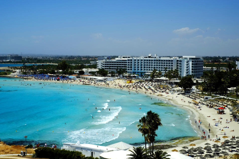 A view of the famous Nissi Beach with people as they enjoy the beach and the sea in southeast resort of Ayia Napa, in the eastern Mediterranean island of Cyprus, Saturday, May 22, 2021. Cypriot hotel and other tourism-related business owners say they'd like to see the COVID-19 pandemic-induced uncertainty over travel bookings to the tourism-reliant island nation winding down by July when they're hoping authorities in Cyprus' main markets including the U.K., Russia, Germany and the Scandinavian countries will make it easier for their citizens to travel abroad. (AP Photo/Petros Karadjias)