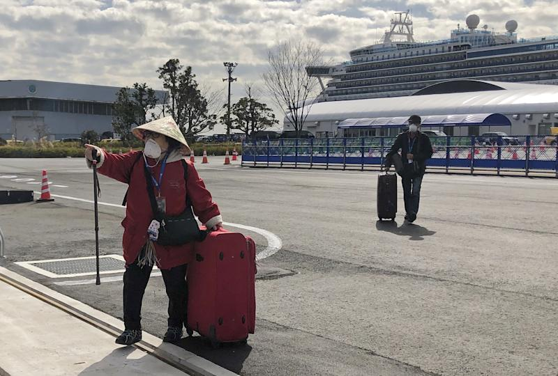 YOKOHAMA, JAPAN - FEBRUARY 19, 2020: Passengers are leaving the Diamond Princess cruise liner, operated by Carnival Corp, after a two-week coronavirus quarantine in the port of Yokohama. The Diamond Princess cruise ship has been quarantined since arriving in Yokohama on February 3, 2020 with more than 3,000 people on board. More than 500 passengers aboard the cruise ship have tested positive for the novel coronavirus since February 4. The outbreak of the 2019-nCoV coronavirus began in Wuhan, China in December 2020. As of 19 February, the number of people in China infected with the new coronavirus has reached more than 74,000, the number of coronavirus cases in Japan has reached 74. Igor Belyayev/TASS (Photo by Igor Belyayev\TASS via Getty Images)