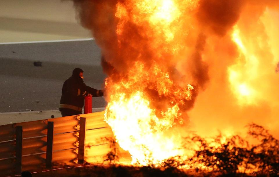 A fire marshal attempts to put out the flames of Romain Grosjean's Haas after an accident on lap one (Reuters)