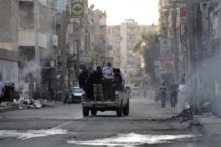 Free Syrian Army fighters ride on the back of a pickup truck in Deir al-Zor