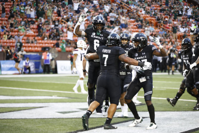 After scoring a second half touchdown, Hawaii running back Dayton Furuta (7) celebrates with his teammates during an NCAA college football game against Arizona, Saturday, Aug. 24, 2019, in Honolulu. (AP Photo/Marco Garcia)