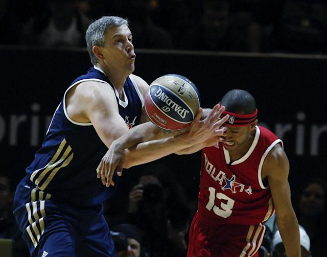 East's United States Secretary of Education Arne Duncan, left, battles West's Terrence Jenkins (13) for a loose ball in the first half as they participate in the NBA All-Star Celebrity basketball game in New Orleans, Friday, Feb. 14, 2014. East won 60-56. (AP Photo/Bill Haber)
