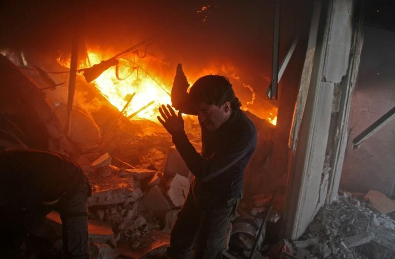 A Syrian man searches for people in a fire following regime air strikes on the rebel-held town of Douma on February 7, 2018