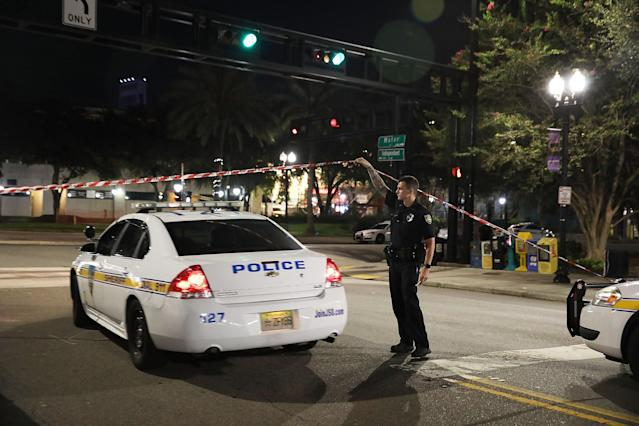 <p>A Jacksonville Sheriff's officer helps keep the perimeter secure as law enforcement investigates a shooting at the GLHF Game Bar which uses the same entrance as the Chicago Pizza place (seen in the center to the rear) at the Jacksonville Landing on Aug. 27, 2018 in Jacksonville, Fla. (Photo: Joe Raedle/Getty Images) </p>