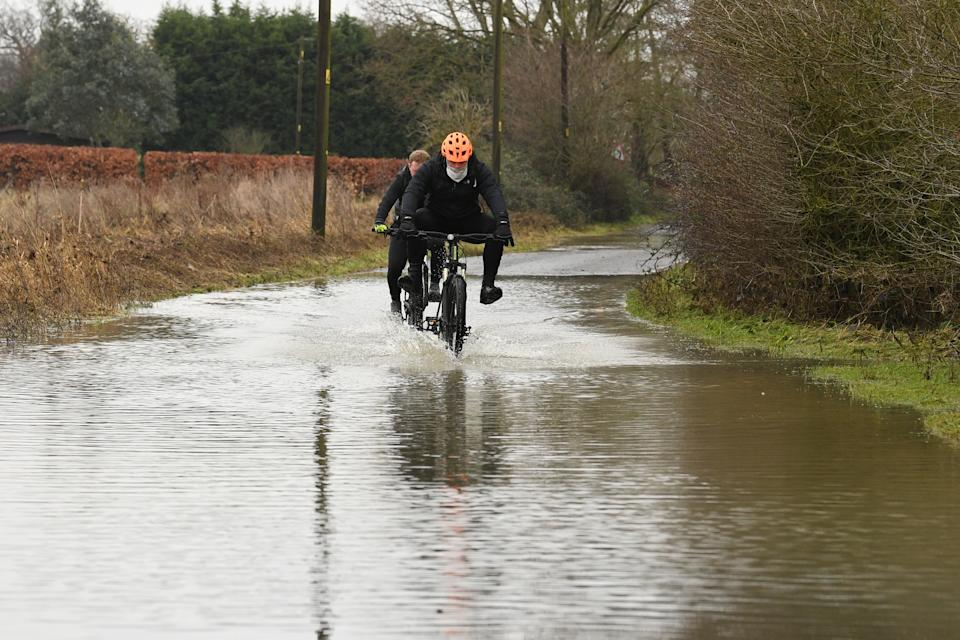 Cyclists make their way through flood water on Mountnessing Road in Billericay, Essex. Heavy snow and freezing rain is set to batter the UK this week, with warnings issued over potential power cuts and travel delays. (Photo by Stefan Rousseau/PA Images via Getty Images)