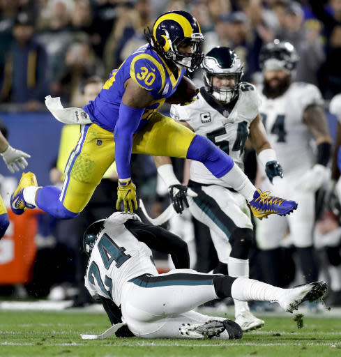 FILE - In this Dec. 16, 2018, file photo, Los Angeles Rams running back Todd Gurley runs over Philadelphia Eagles free safety Corey Graham during the first half in an NFL football game, in Los Angeles. Gurley is a big football fan, and Ezekiel Elliott is one of his favorite players. The good feelings are mutual heading into the Cowboys' playoff visit to the Rams and a showdown between the NFL's two premiere running backs. (AP Photo/Marcio Jose Sanchez, File)