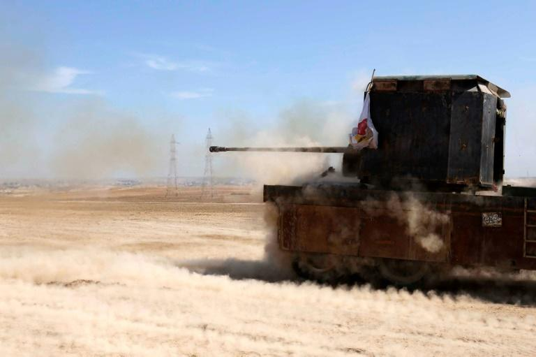Iraqi fighters from the Abbas Brigade fire toward enemy positions from Badush