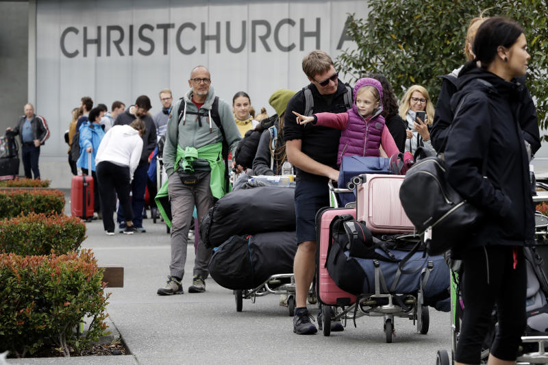 FILE - In this April 6, 2020, file photo, foreign tourists queue outside the terminal at Christchurch Airport terminal as they prepare to check in for a charter flight back to Germany via Vancouver from Christchurch, New Zealand. New Zealand has set itself an ambitious goal of not just containing the coronavirus, but eliminating it altogether. Experts believe the country could pull it off, thanks to its geography and decisive early actions by Prime Minister Jacinda Ardern, who has put the country into a strict lockdown. But whatever happens, the country will continue feeling the effects of the pandemic, which has hobbled its vital tourism industry. (AP Photo/Mark Baker, File)