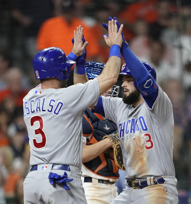 Chicago Cubs' David Bote (13) celebrates with Daniel Descalso (3) after both scored on Bote's home run against the Houston Astros during the sixth inning of a baseball game Tuesday, May 28, 2019, in Houston. (AP Photo/David J. Phillip)