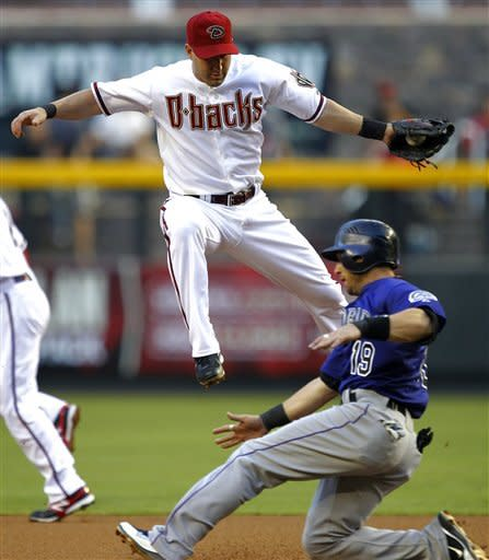 Colorado Rockies' Marco Scutaro (19) safely steals second as Arizona Diamondbacks' Willie Bloomquist makes the catch during the first inning of a baseball game, Tuesday, June 5, 2012, in Phoenix. (AP Photo/Matt York)