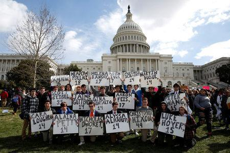Students from Gonzaga College High School in Washington, DC, hold up signs with the names of those killed in the Parkland, Florida, school shooting during a protest for stricter gun control during a walkout by students at the U.S. Capitol in Washington, U.S., March 14, 2018. REUTERS/Joshua Roberts TPX IMAGES OF THE DAY - RC1B22FFFCF0