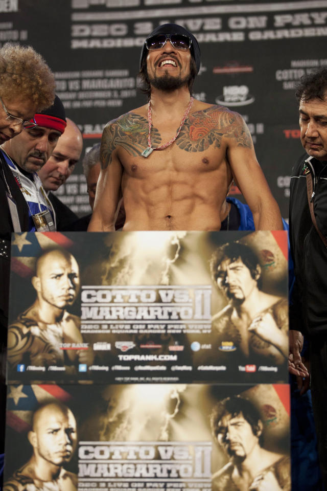 Boxer Antonio Margarito of Mexico stands on a scale during the official weigh-in for his fight against Miguel Cotto of Puerto Rico at Madison Square Garden in New York December 2, 2011. Margarito weighed in at 153 lbs (69 kg). The fight will take place on December 3. (REUTERS/Andrew Burton)
