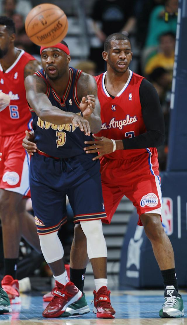Denver Nuggets guard Ty Lawson, left, passes ball while covered by Los Angeles Clippers guard Chris Paul in the first quarter of an NBA basketball game in Denver on Monday, March 17, 2014. (AP Photo/David Zalubowski)