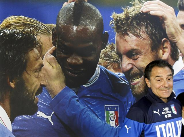 Italy coach Cesare Prandelli stands in front of a poster showing players, from left, Andrea Pirlo, Mario Balotelli, and Daniele De Rossi during a press conference at the national team's Coverciano training complex in Florence, Italy, Tuesday, April 15, 2014, where 42 players were called up for World Cup fitness tests. (AP Photo/Fabrizio Giovannozzi)