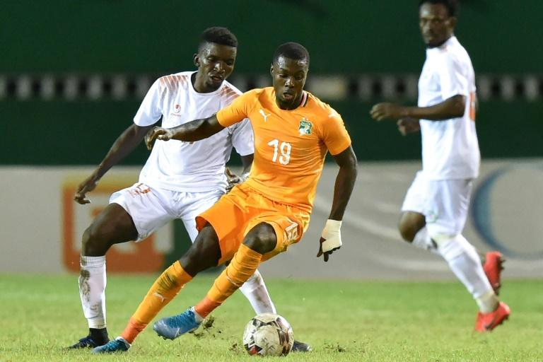 Ivory Coast forward Nicolas Pepe (C) controls the ball with Niger midfielder Mahamane Cisse behind him during an Africa Cup of Nations qualifier in Abidjan Saturday