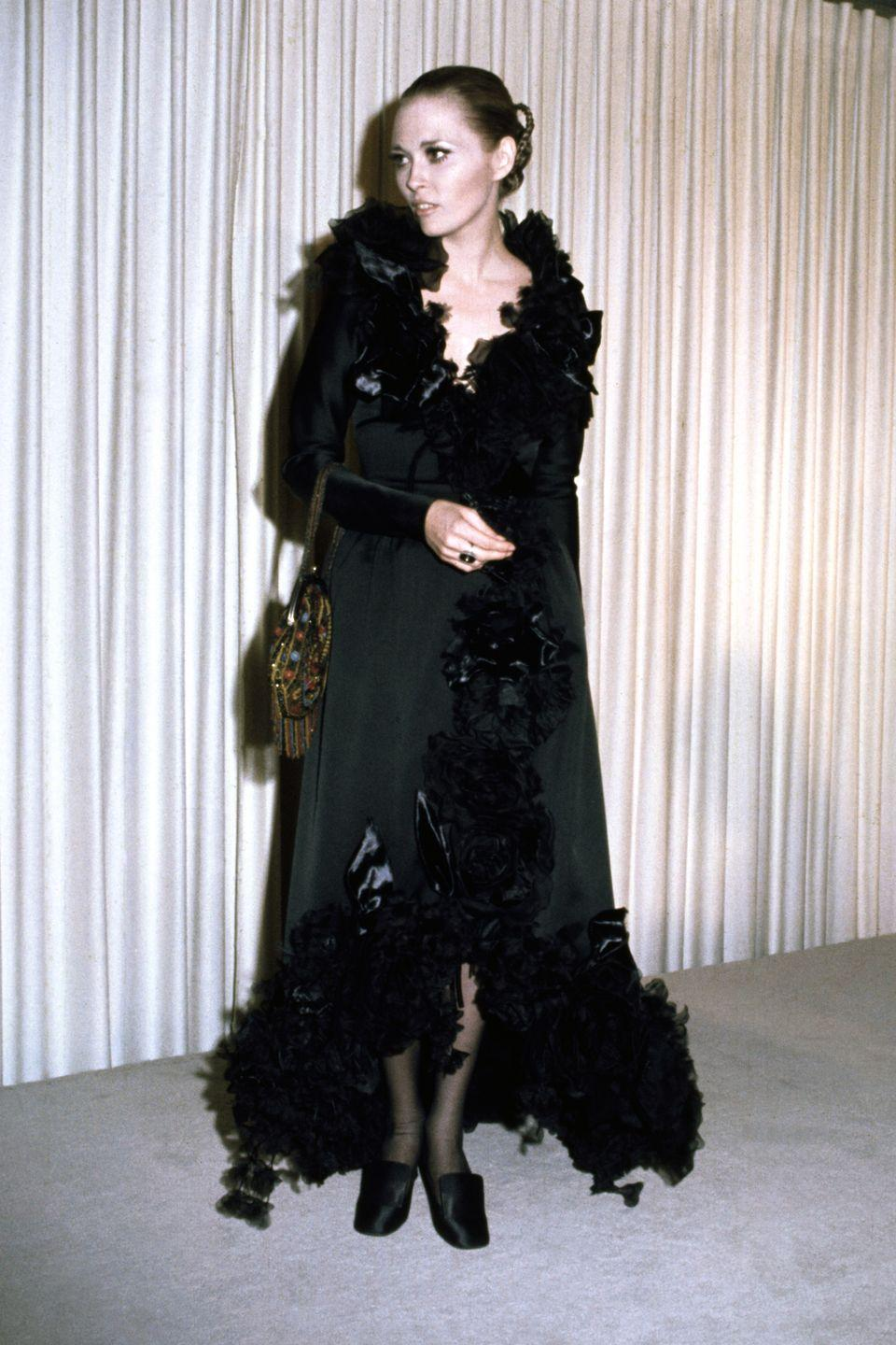 <p>Faye Dunaway brought the drama in a black ruffled wrap dress, and slicked back hair. </p>