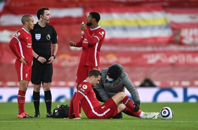 Jordan Henderson is checked by medical staff on the pitch
