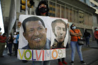 """A government supporter holds photos of late Venezuelan President Hugo Chavez, left, and independence hero Simon Bolivar with the Spanish message """"We're back"""" outside the National Assembly where lawmakers are being sworn-in, in Caracas, Venezuela, Tuesday, Jan. 5, 2021. The ruling socialist party assumed the leadership of Venezuela's congress on Tuesday, the last institution in the country it didn't already control. (AP Photo/Ariana Cubillos)"""
