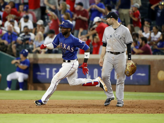 Texas Rangers' Jurickson Profar (19) runs past New York Yankees first baseman Neil Walker on a two-run double during the sixth inning of a baseball game Wednesday, May 23, 2018, in Arlington, Texas. (AP Photo/Michael Ainsworth)