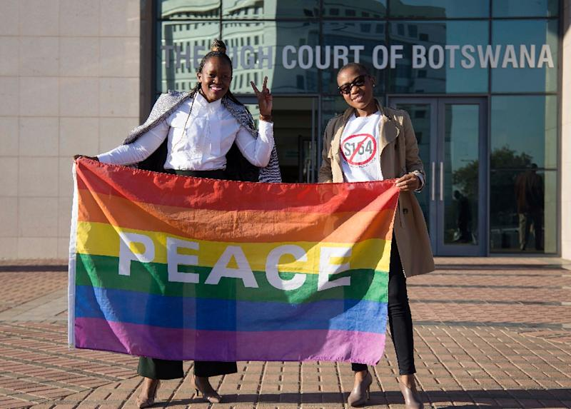 Activists pose with a rainbow flag as they celebrate the Botswana High Court's decision to decriminalize same-sex relationships