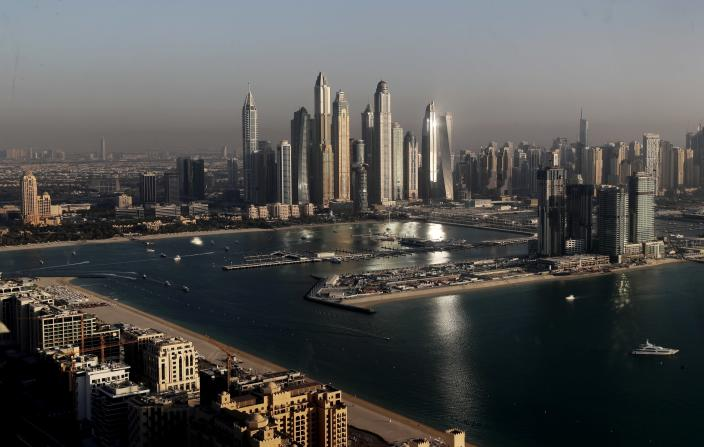 """Luxury towers dominate the skyline in the Marina district, center, and the new Dubai Harbour development, right, are seen from the observation deck of """"The View at The Palm Jumeirah"""" in Dubai, United Arab Emirates, Tuesday, April 6, 2021. Foreign buyers flush with cash have flooded the high-end property market in Dubai even as coronavirus vaccines roll out unevenly across the world and waves of infections force countries to extend restrictions. It's one of the few places in the world where they can dine, shop and do business in person. (AP Photo/Kamran Jebreili)"""