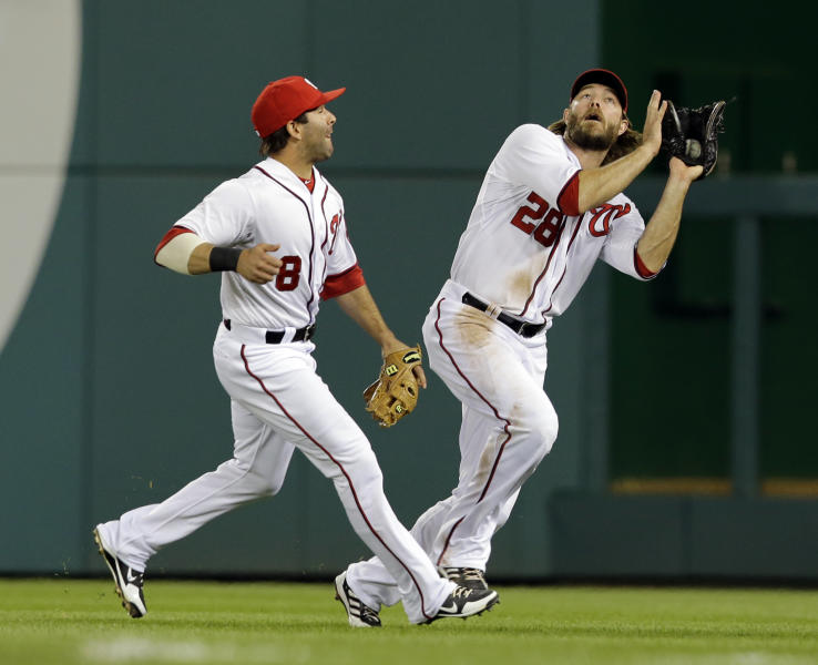 Washington Nationals right fielder Jayson Werth (28) catches a fly hit by Cincinnati Reds' Corky Miller, as second baseman Danny Espinosa (8) almost collides with Werth, during the fifth inning of a baseball game at Nationals Park Friday, April 26, 2013, in Washington. (AP Photo/Alex Brandon)