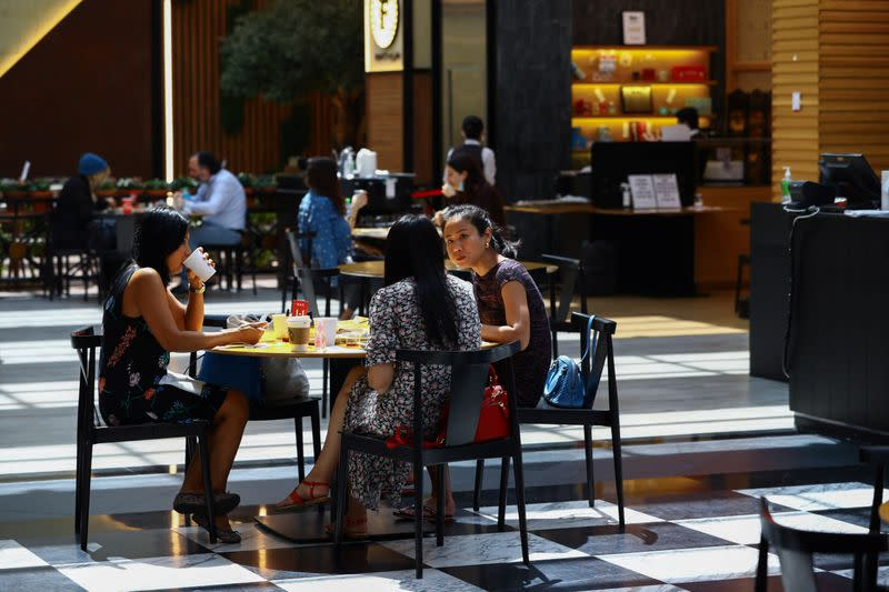 People sit in a coffee shop during the reopening of malls, following the outbreak of the coronavirus disease (COVID-19), at Mall of the Emirates in Dubai