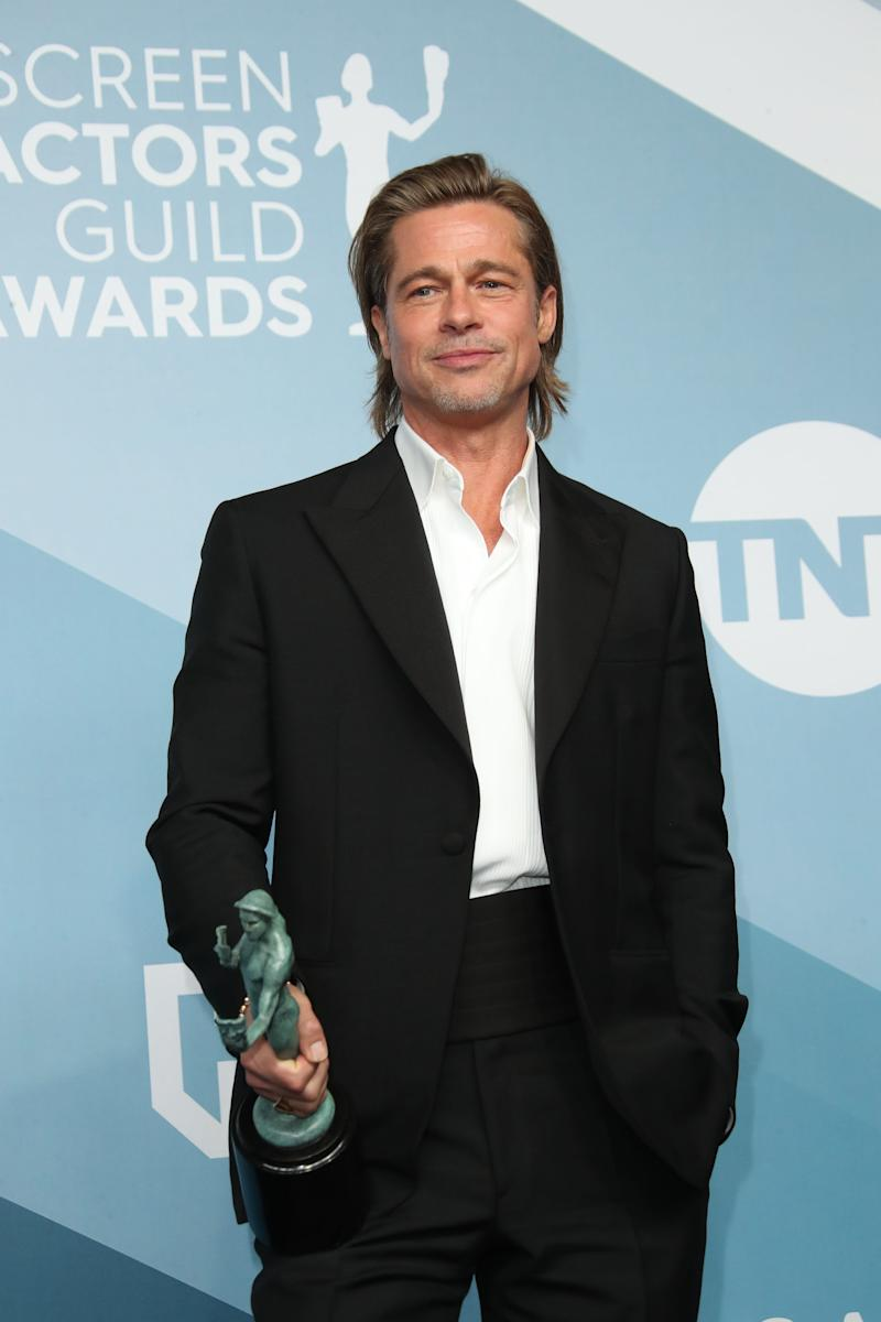 "Brad Pitt poses with his best supporting actor award for ""Once Upon a Time in Hollywood"" at the 26th annual Screen Actors Guild Awards."