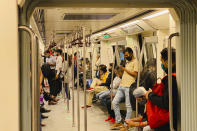 Commuters wear face masks as a precautionary measure against the coronavirus and travel in a metro train in New Delhi, India, Friday, Nov. 6, 2020. (AP Photo/Rajesh Kumar Singh)