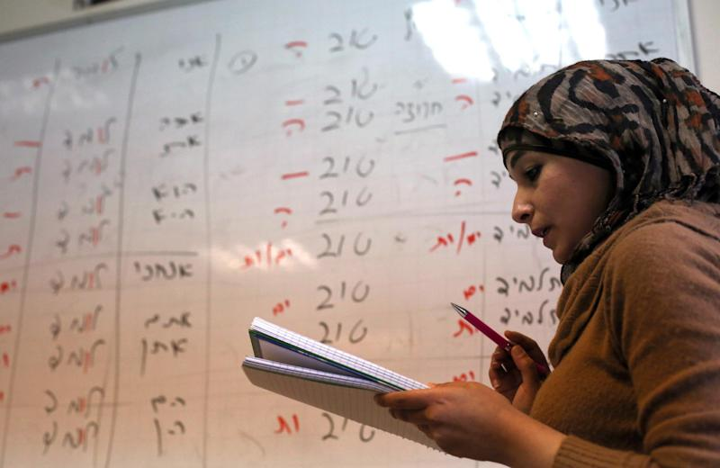 A Palestinian student looks at a notepad during a Hebrew language course at the Nasser al-Shiukhi college in the West Bank city of Ramallah (AFP Photo/Abbas Momani)