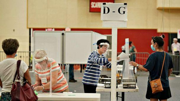 PHOTO: Election workers assist voters at Scarborough High School, July 14, 2020, in Scarborough, Maine. (Portland Press Herald via Getty Images)