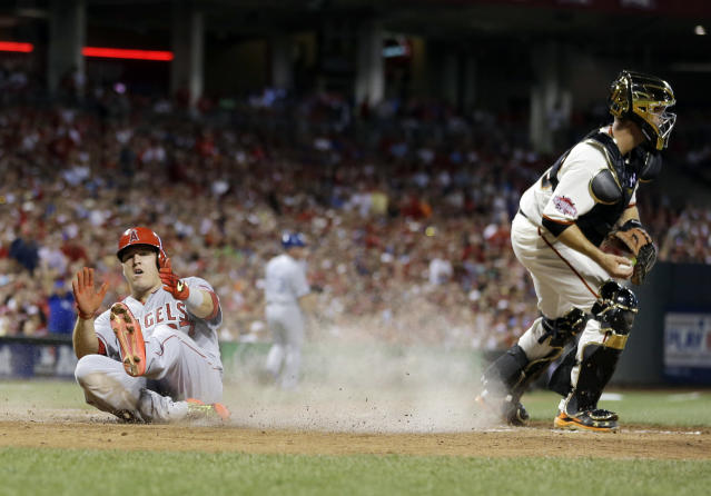American League's Mike Trout, of the Los Angeles Angels, scores on a hit by American League's Prince Fielder, of the Texas Rangers, during the fifth inning of the MLB All-Star baseball game, Tuesday, July 14, 2015, in Cincinnati. (AP Photo/Jeff Roberson)