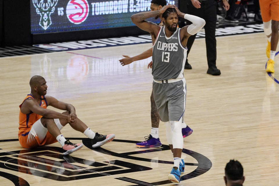 Los Angeles Clippers guard Paul George, right, reacts after fouling Phoenix Suns guard Chris Paul, left, during the second half in Game 4 of the NBA basketball Western Conference Finals Saturday, June 26, 2021, in Los Angeles. (AP Photo/Mark J. Terrill)