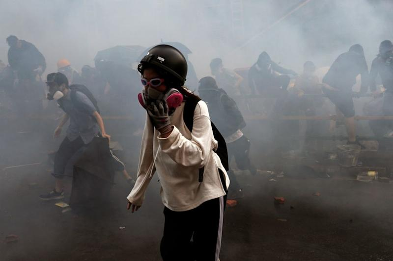 Protesters attempt to escape from tear gas while trying to leave the Polytechnic University campus on Monday