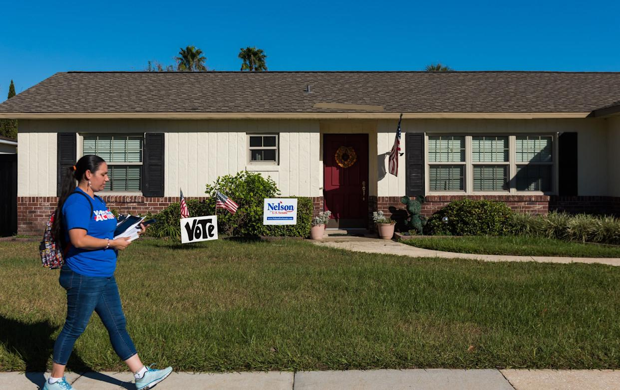 Arleen Sevilla walks by a house with signs supporting Sen. Bill Nelson (D-Fla.) while canvassing in Orlando. (Photo: Chris McGonigal/HuffPost)