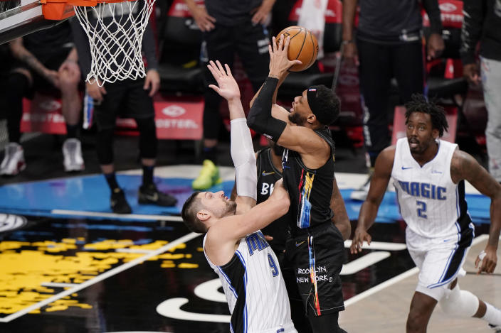 Orlando Magic center Nikola Vucevic (9) defends against Brooklyn Nets guard Bruce Brown (1) as Magic forward Al-Farouq Aminu (2) looks on during the third quarter of an NBA basketball game, Thursday, Feb. 25, 2021, in New York. (AP Photo/Kathy Willens)