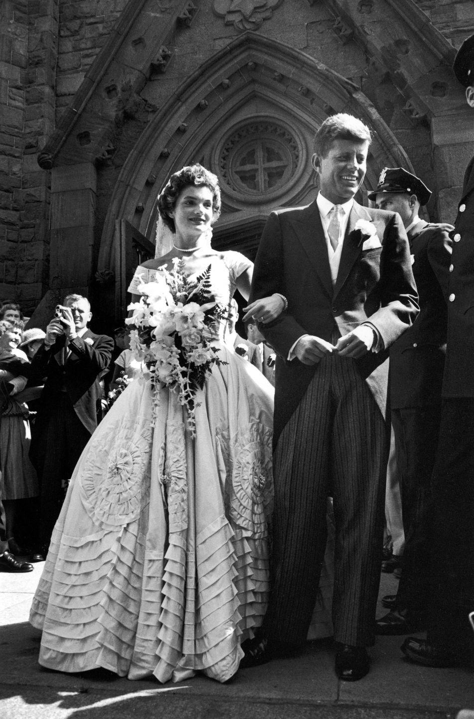"""<p>Jacqueline Bouvier married John F. Kennedy on September 12, 1953 in Newport, Rhode Island. Her gorgeous wedding gown was created by African-American fashion designer <a href=""""https://www.racked.com/2016/9/30/13064294/fashion-designer-ann-lowe"""" rel=""""nofollow noopener"""" target=""""_blank"""" data-ylk=""""slk:Ann Lowe"""" class=""""link rapid-noclick-resp"""">Ann Lowe</a>—who didn't receive credit for the dress until much later in life—and is now on display at the Kennedy Library in Boston. The dress consisted of 50 yards of fabric made out of <a href=""""https://www.vogue.com/article/jackie-kennedy-wedding-to-john-f-kennedy"""" rel=""""nofollow noopener"""" target=""""_blank"""" data-ylk=""""slk:ivory-colored silk taffeta"""" class=""""link rapid-noclick-resp"""">ivory-colored silk taffeta</a> and Jackie wore a lace wedding veil that belonged to her grandmother. She also wore a single strand pearl necklace, which was a family heirloom, and a diamond pin from her parents and a diamond bracelet from her groom. </p>"""