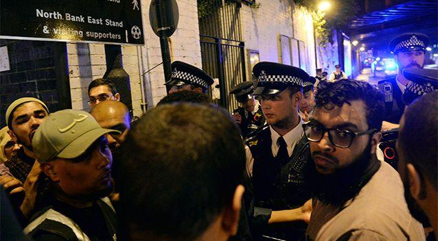 Police and civilians gather in front of the mosque after the attack. Photo: AP