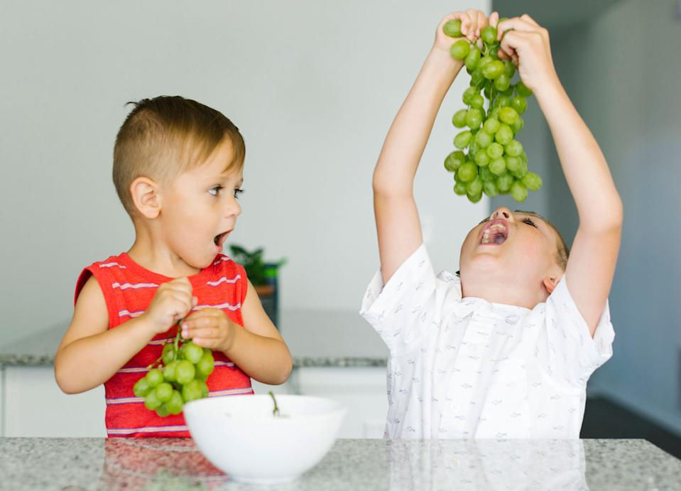 Two young boys eating grapes.
