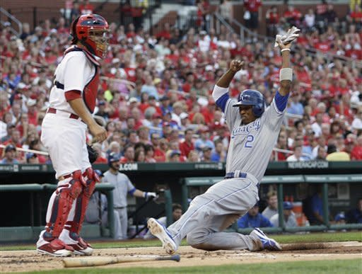 Kansas City Royals' Alcides Escobar (2) scores from third on an infield single by Jarrod Dyson as St. Louis Cardinals catcher Yadier Molina waits for a throw in the second inning of a baseball game, Friday, June 15, 2012 in St. Louis.(AP Photo/Tom Gannam)