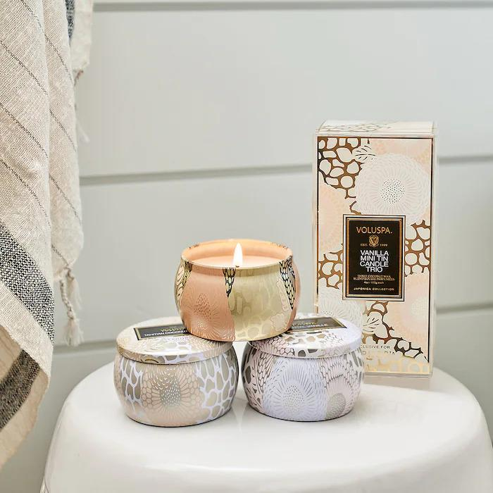 Three mini candle tins places on a white side table