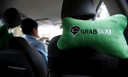 A GrabTaxi logo is seen on a car neck pillow in a taxi in Hanoi