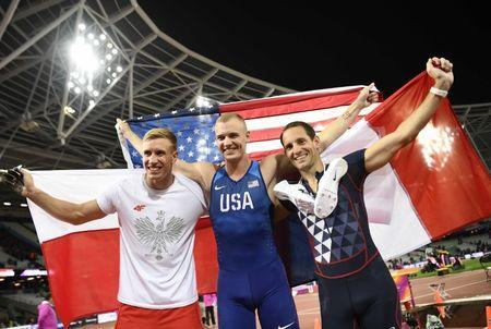 Athletics - World Athletics Championships –men's pole vault final – London Stadium, London, Britain – August 8, 2017 – Piotr Lisek of Poland, Renaud Lavillenie of France and Sam Kendricks of the U.S. celebrate after the final. REUTERS/Dylan Martinez