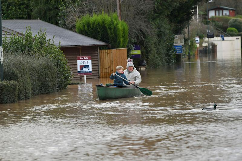 Nearby residents making their way through floodwater by boat in Monmouth. (Photo: ASSOCIATED PRESS)