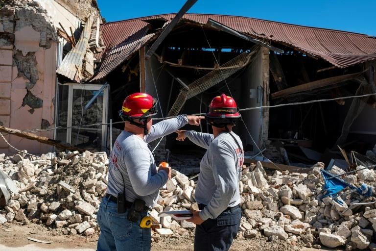 Two firemen survey a collapsed building after an earthquake hit Guanica, one of the towns which appeared to suffer the worst damage on Puerto Rico's southwest coast (AFP Photo/Ricardo ARDUENGO)