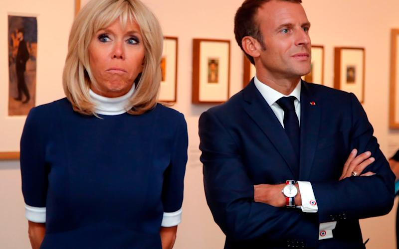 French President Emmanuel Macron (R) and his wife Brigitte Macron (C) visit the